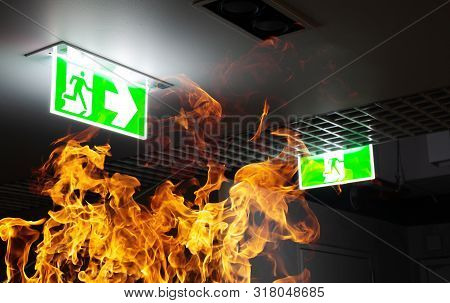 Hot Flame Fire And Green Fire Escape Sign Hang On The Ceiling In The Office At Night. The Concept Of