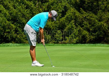 Young Man Playing Golf Looking Down At The Green And Concentrating On His Putt Shot.