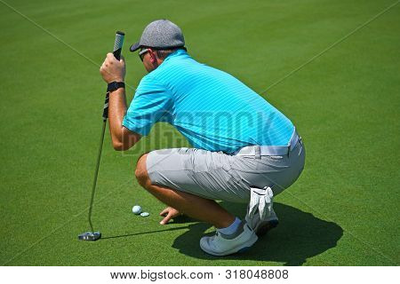 Shallow Dof Image Of A Young Man Playing Golf Squatted Down Looking Over The Green Before Making His