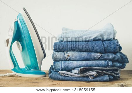 Stack Of Clothes And Electric Iron On Table Indoor. Household Concept. Fresh Folded Cotton Jeans Clo