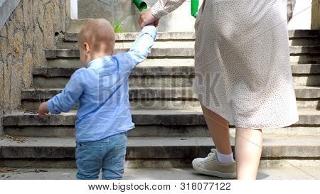 Close-up Of Mother And Child Climb Steps. Stock Footage. Back View Of Mother In Dress And Son Climbi