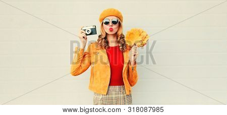 Woman Holding Autumn Yellow Maple Leaves, Camera Taking Picture And Blowing Red Lips Sending Sweet A