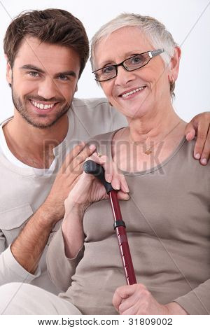 Smiling young man with his arms around a senior woman in glasses