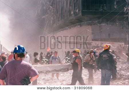NEW YORK - SEPTEMBER 11: Emergency workers and journalists stand near the area known as Ground Zero after the collapse of the Twin Towers on September 11, 2001 in New York City.