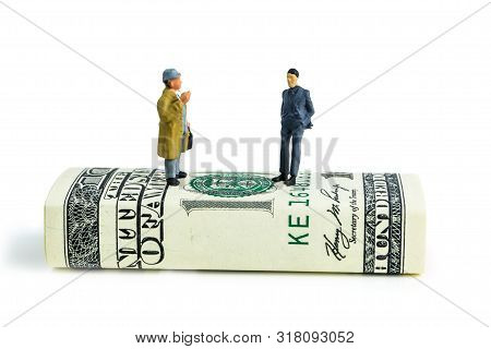 Miniature Figurines Of Businessmen Standing On One Hundred Dollar Banknote And Making Economic Decis