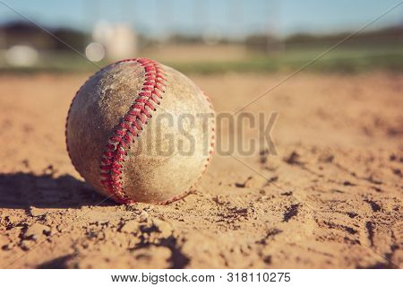 Baseball sitting in the dirt of the infield