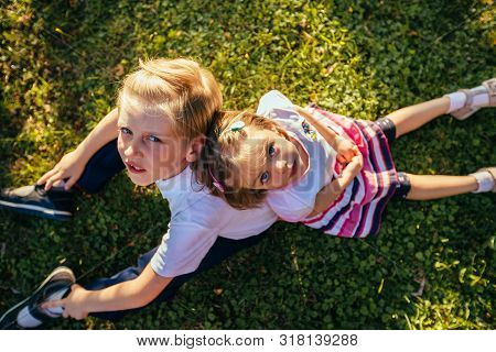 Top View Two Children Sitting On The Grass An Summer Time, Looking In Camera. Brother And Sister Loo