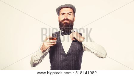 Bearded In Is Holding A Glass Of Whiskey. Sommelier Tastes Expensive Drink. Handsome Well-dressed Ma