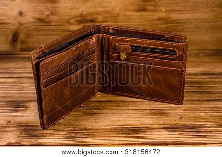 Opened Brown Leather Wallet On Rustic Wooden Table