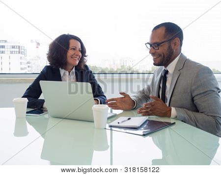 Happy Coworkers Discussing New Business Software. Business Man And Woman Sitting At Meeting Table Wi