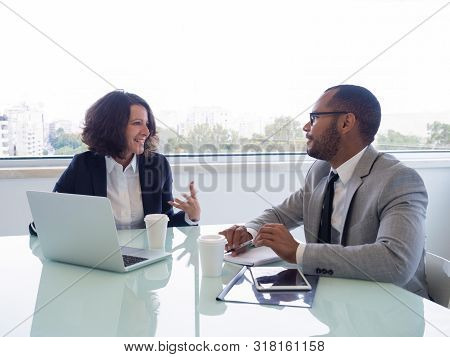 Happy Female Mentor Explaining Work Issues To Male Intern. Business Man And Woman Sitting At Meeting