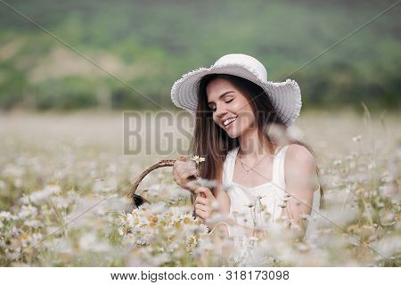 Beautiful Girl Outdoors With A Bouquet Of Flowers In A Field Of White Daisies,enjoying Nature. Beaut