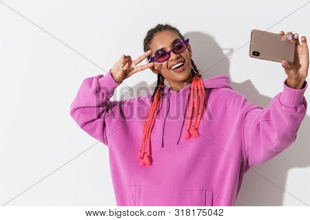 Image of happy positive smiling young african woman isolated over white wall background in bright pink sweatshirt wearing sunglasses take a selfie by mobile phone with peace.