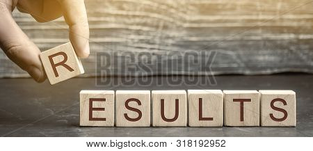 Businessman Puts Wooden Blocks With The Word Results. The Concept Of Annual Financial Statements. An