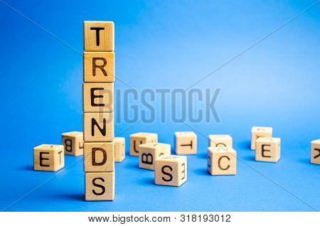 Wooden blocks with the word Trends. Popular and relevant topics. New ideological trends of fashion. Recent and latest trend. Evaluation methods. poster