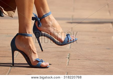 Stiletto Heels, Female Feet In High-heeled Summer Shoes. Stylish Woman With Pedicure Sitting On A Ci