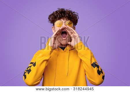 Stylish youngster in yellow hoodie and sunglasses keeping hands near mouth and screaming at camera while standing against bright violet background poster
