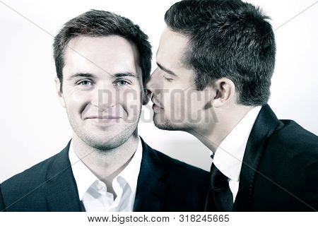 Portrait Of Attractive Gay Couple With One Smiling At Camera As The Other Is About To Kiss His Cheek