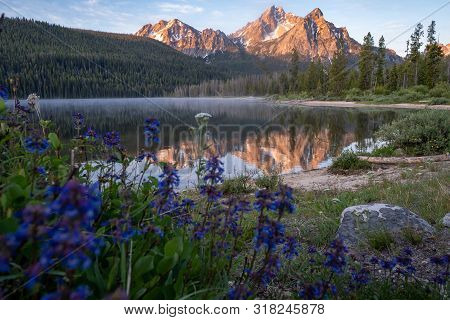 Beautiful Sunrise At Stanley Lake In The Sawtooth Mountains Of Idaho. Reflection In Water With Wildf
