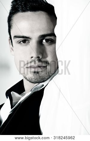 Portrait Of Good Looking Man With Goatee Looking At Camera Isolated Against White Wall.