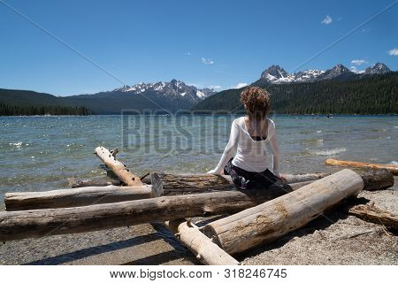 Adult Woman (30-35 Years) Sits On A Pile Of Logs On The Shoreline Of Redfish Lake In Stanley Idaho I