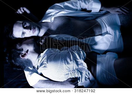 Gay Male Couple Lying In Bed With One Looking At Camera As He Is Being Cuddled By His Partner