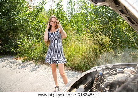 The young woman broke down the car while traveling on the way to rest. She is trying to fix the broken by her own or should hitchhike. Getting nervous. Weekend, troubles on the road, vacation. poster