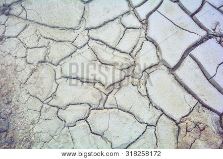 Dry Mud Ground With Crack Texture And Granite Gravel. Dry Dirty Soil On Summer Landscape. Cracks On