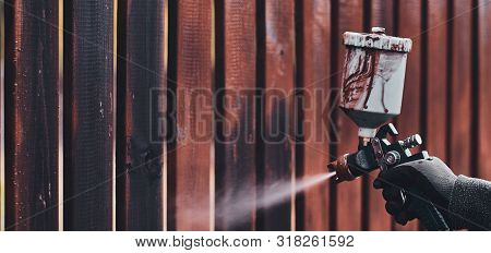Process Of Old Fence Renovation By Worker In Protective Gloves. He Is Usin Airbrush, Applying Paint.