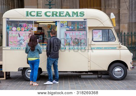 Edinburgh, Scotland - 9th August 2015: Traditional ice cream van parked in the street in Edinbiugh. A man and a woman are purchasing refreshments.