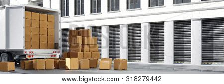 Truck from forwarding or moving company with many boxes in front of a warehouse (3D Rendering)