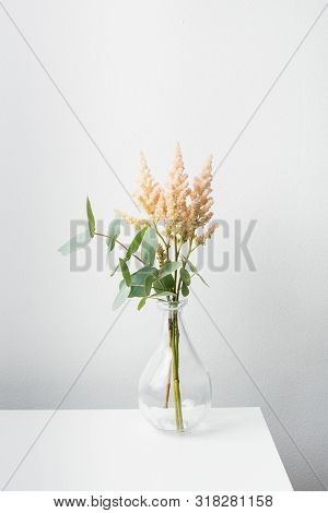 Small Bouquet Of Flowers In Vase On White Table