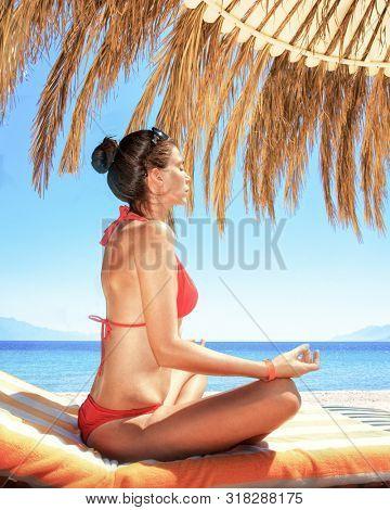 girl meditates on the hotel beach