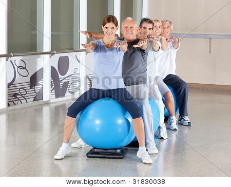 Senior group in gym balls exercising in fitness center