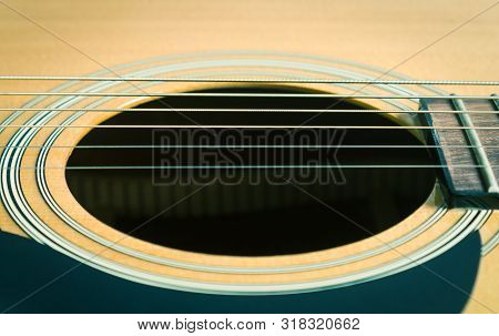Sound Hole And Acoustic Guitar String And Pickguard And Fingerboard And Fret In Close Up View