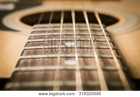 Close Up Fingerboard And Inlay Of 6 String Brown Wood Acoustic Guitar