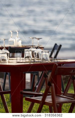 Tables In Outdoor Cafe Or Restaurant Served For Dinner On Beach With Sea View