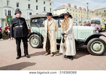 Llandudno, North Wales- 29th April 2017: People Dressed In Victorian Costume Standing Alongside A Vi