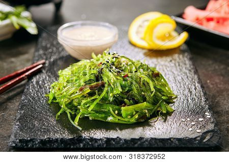 Macro shot of hiyashi wakame chuka or kelp salad on natural black slate plate background. Seaweed food salat with sesame and nut sauce in Japanese restaurant closeup
