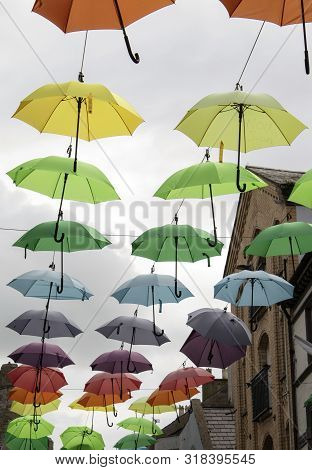 Wales, The Historic Town City Of Caernarfon.  Inside The Walled Town, Jolly, Coloured Umbrellas Are