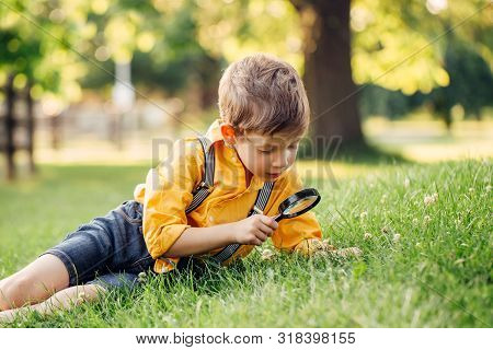 Cute Adorable Caucasian Boy Looking At Plants Grass Flowers In Park Through Magnifying Glass. Kid Wi