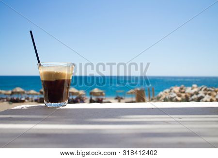 Glass With Ice Coffee Fredo Espresso Or Frappe On The Corner Of The Table With Beach On Background
