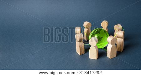 People Surrounded A Green Globe World Planet Earth. Diplomacy And Crowdfunding. Concept Of Cooperati