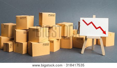 Lots Of Boxes And An Easel With A Red Down Arrow. Slowdown In Industrial Production And Sales Fall.