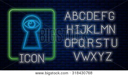 Glowing Neon Keyhole With Eye Icon Isolated On Brick Wall Background. The Eye Looks Into The Keyhole