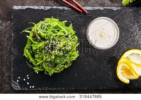 Top View of hiyashi wakame chuka or kelp salad on natural black slate plate background. Seaweed food salat with sesame and nut sauce in Japanese restaurant closeup