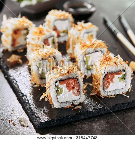 Macro shot of uramaki sushi rolls with cream cheese, salmon, tuna shavings or dried bonito, cucumber, nori. Portion of fresh katsuobushi roll in Japanese restaurant closeup