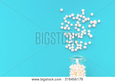 Homeopathic Globules In Glass Bottle On Pastel Blue Background. The Globules Are Scattered From Bott
