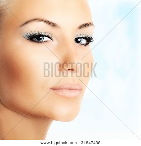 Closeup of beautiful female face over abstract blue sky background, bright eye makeup, sexy woman with perfect soft skin, female beauty care and glamourous style