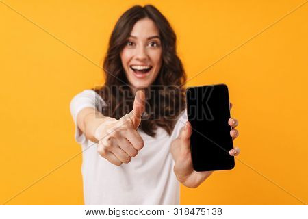 Image of happy positive smiling young woman posing isolated over yellow wall background using mobile phone showing display and thumbs up.